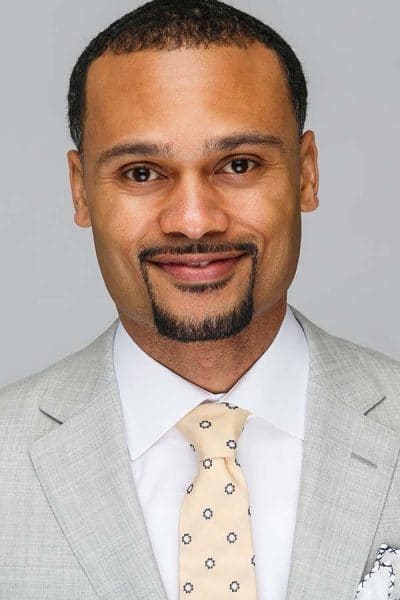 black man headshot grey suit yellow tie